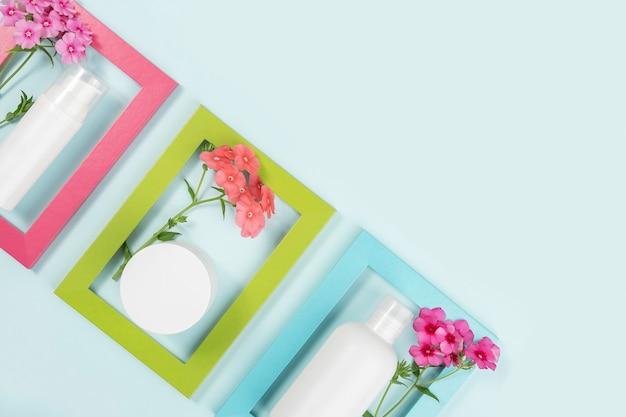 Frasco cosmético em branco branco, tubo, frasco, flores em quadros brilhantes na superfície azul