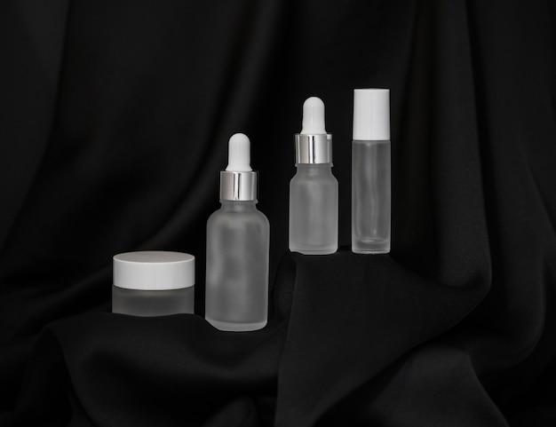 Frasco cosmético, spray e dois frascos de cosméticos com um conta-gotas em um fundo de seda preta, spray cosmético e um porta-frasco pequeno na plataforma acima