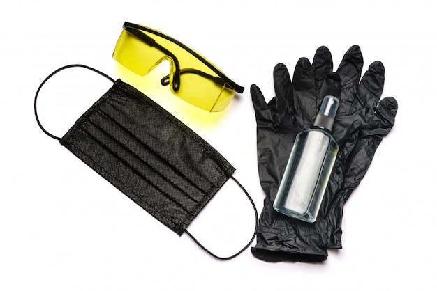 Frasco da loção, do desinfetante ou do sabonete líquido, dos óculos de proteção e da máscara protetora isolados na parede branca com trajeto de grampeamento.