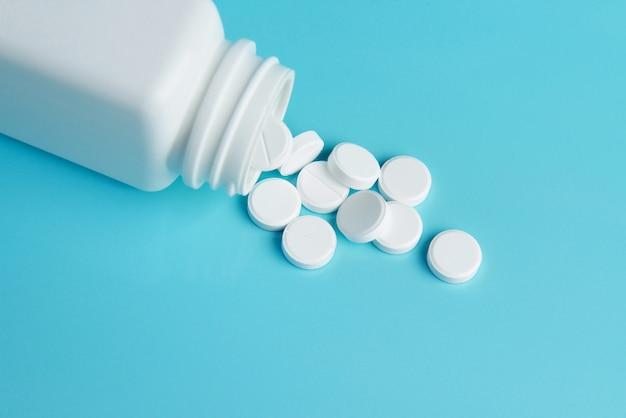 Frasco da medicamentação e comprimidos brancos.