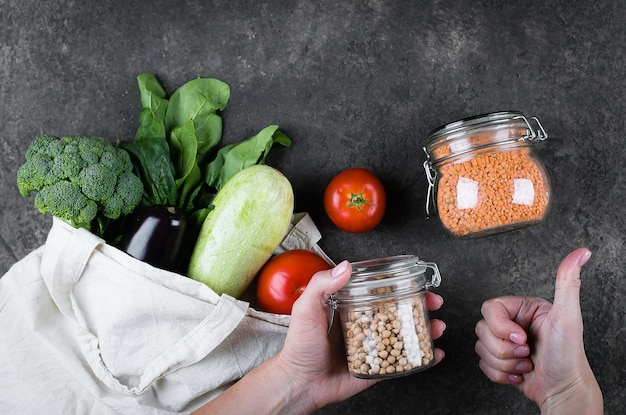 Frasco da terra arrendada da mulher com grãos-de-bico. legumes, saco reutilizável. jarra de vidro - lentilhas. conceito de desperdício zero