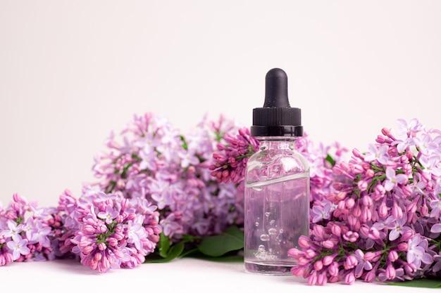 Frasco de ácido hialurônico e lilás em uma superfície branca