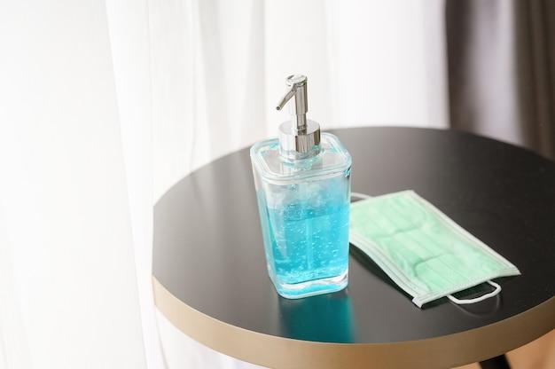 Frasco de álcool gel desinfetante para as mãos para higiene das mãos e máscaras médico-cirúrgicas na mesa da casa
