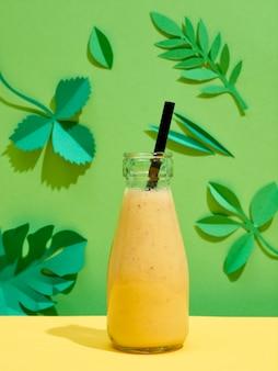 Frasco de banana amarela, suco de abacaxi e suco de manga com canudo preto sobre fundo colorido com folhas de papel verde