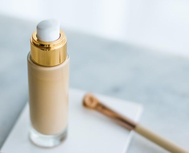 Frasco de base de maquiagem de conceito de marca cosmética e pincel de contorno em mar ...
