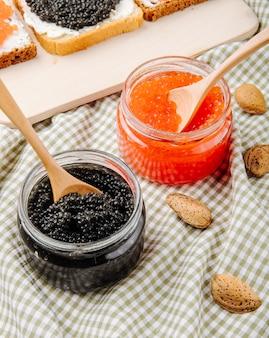 Frasco de caviar preto e vermelho de vista lateral com colher de pau e amêndoa em cima da mesa