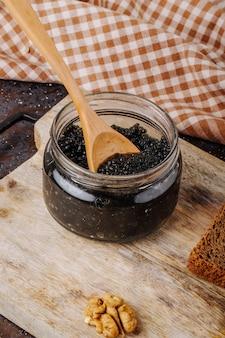 Frasco de caviar preto vista lateral com superfície de madeira pão de centeio e nozes em uma placa