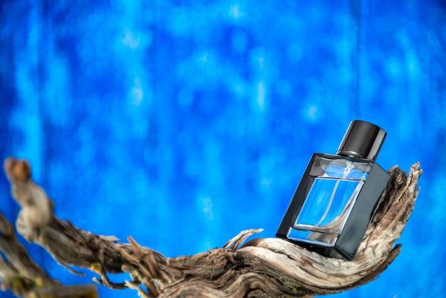 Frasco de colônia de vista frontal em um galho de madeira podre em fundo azul