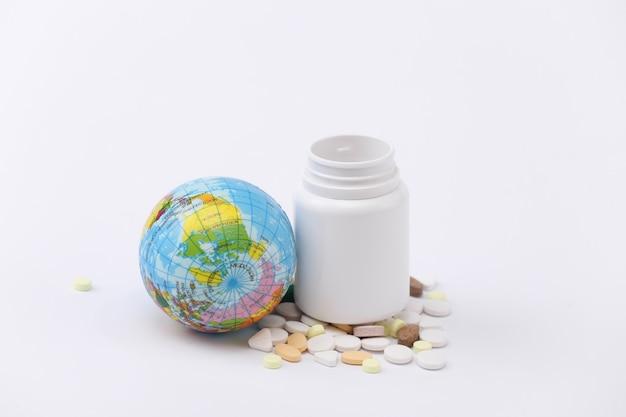 Frasco de comprimidos com globo em fundo branco close-up