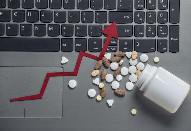 Frasco de comprimidos com seta de crescimento no teclado do laptop