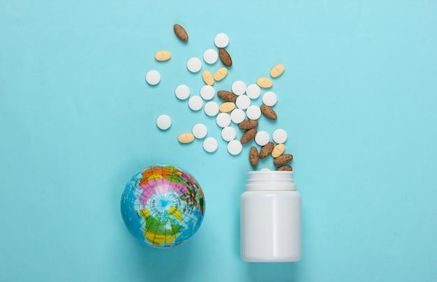Frasco de comprimidos com um globo em um azul. pandemia mundial