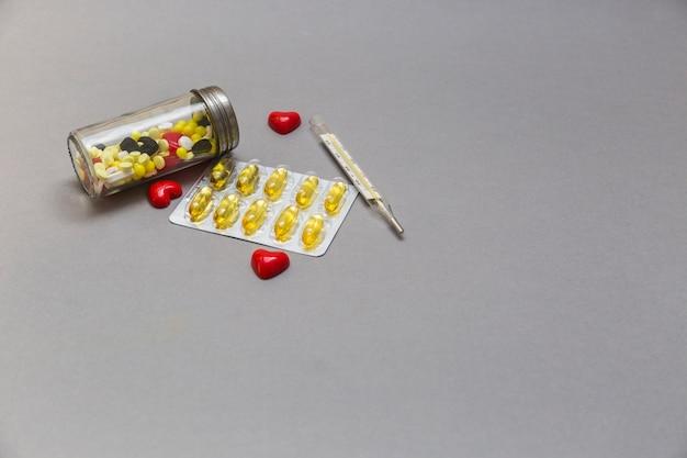Frasco de comprimidos; coração vermelho e termômetro no fundo cinzento