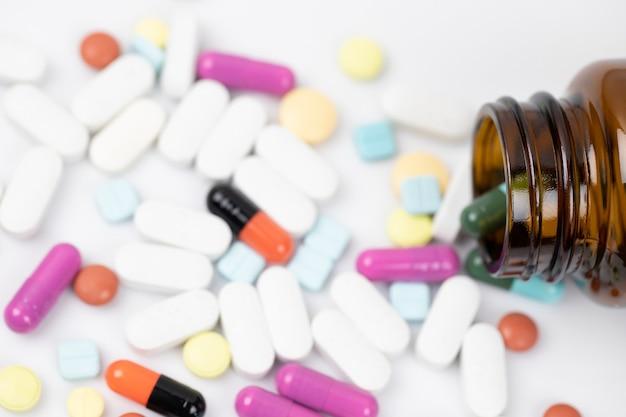 Frasco de comprimidos derramando. cápsula de comprimidos coloridos para comprimidos de superfície em um fundo branco.