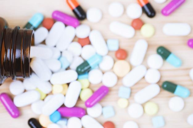 Frasco de comprimidos derramando. cápsula de comprimidos coloridos sobre comprimidos de superfície