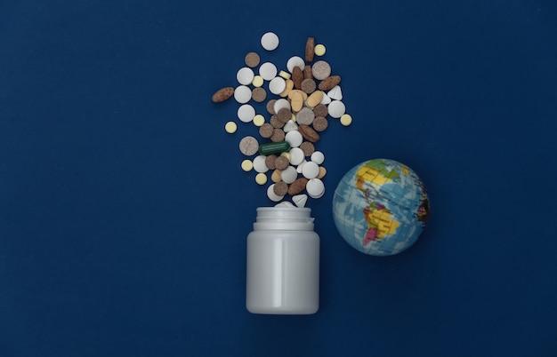 Frasco de comprimidos e globo em fundo azul clássico. cor 2020. vista superior.