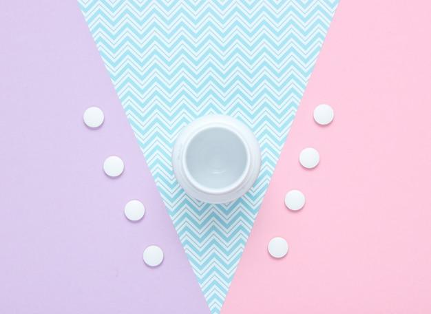Frasco de comprimidos na mesa de papel pastel. vista do topo