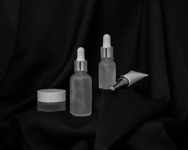 Frasco de cosmético, spray e dois frascos de cosméticos com um conta-gotas em um fundo de seda preta, tubo de cosmético e um pequeno suporte de frasco na plataforma acima
