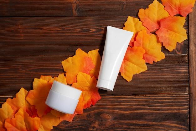 Frasco de creme branco e tubo de cosméticos para cuidados com a pele no fundo de madeira marrom outono plano plano