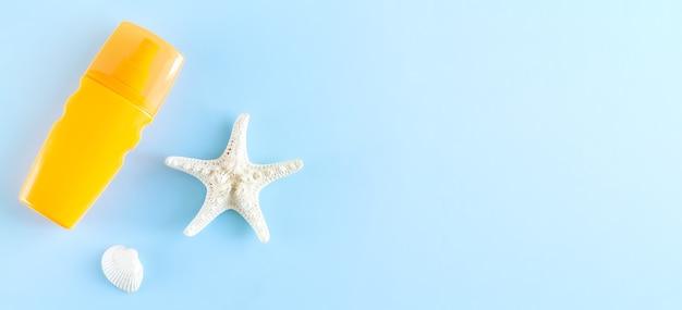 Frasco de creme protetor solar de verão ao lado da concha do mar e estrela do mar na vista superior do fundo azul