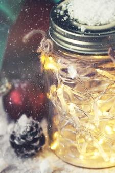 Frasco de cristal com luzes com um presente ao lado dele ao nevar estreitamente