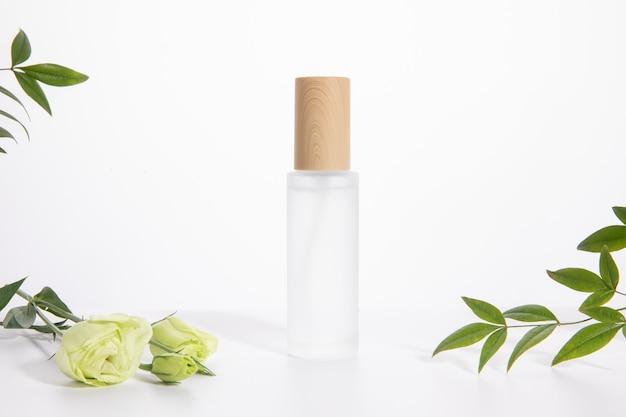 Frasco de cuidado de pele único em um fundo branco com uma rosa e folhas verdes