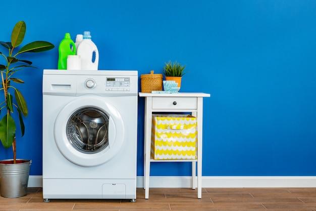 Frasco de detergente com máquina de lavar roupa, dentro de casa