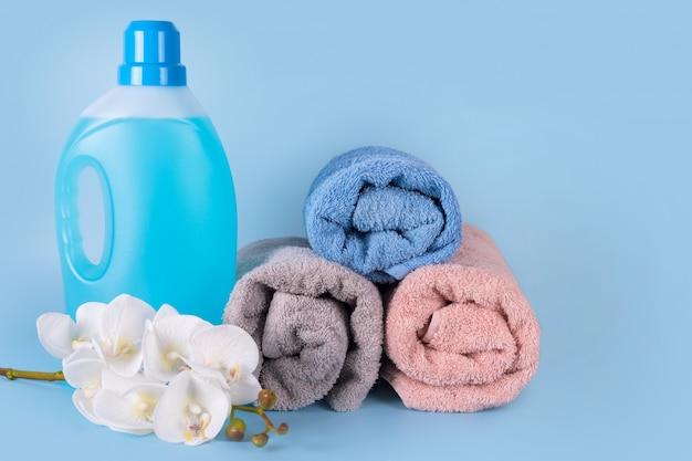 Frasco de detergente com toalhas limpas e flores sobre fundo azul