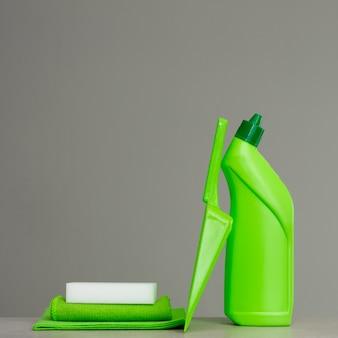 Frasco de detergente verde para banheiro, esponja, colher e pano de pó. ferramentas de limpeza.