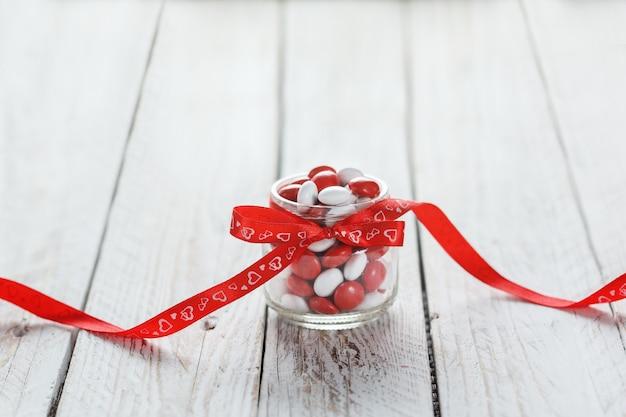 Frasco de doces coloridos decorado com um laço vermelho de corações. conceito dia dos namorados