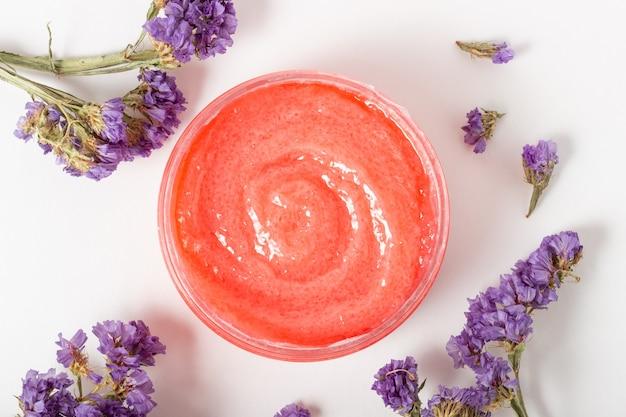 Frasco de esfoliante facial cosmético com flores e óleos essenciais. cosméticos orgânicos, cosméticos próprias mãos. salão spa, cuidados com a pele