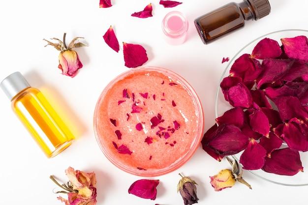 Frasco de esfoliante facial cosmético com pétalas de rosa e óleos essenciais. cosméticos orgânicos. salão spa, cuidados com a pele