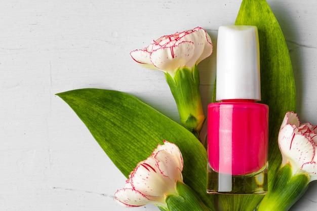 Frasco de esmalte rosa com botões de flores