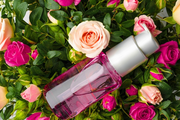 Frasco de fragrância ou óleo aromático em um ramo de flores frescas