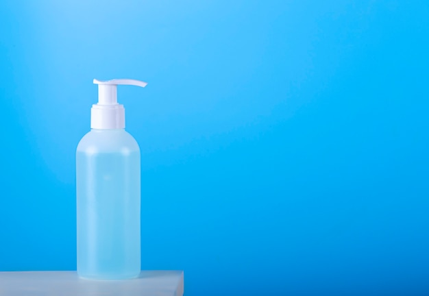 Frasco de gel anti-séptico de mão isolado sobre fundo azul.