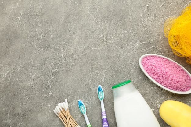 Frasco de gel de banho rosa, sabonete, sal de banho e escova de dentes na parede cinza. vista do topo