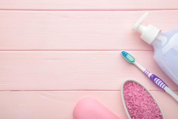 Frasco de gel de banho rosa, sabonete, sal de banho e escova de dentes na parede rosa. vista do topo