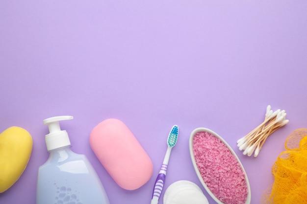 Frasco de gel de banho rosa, sabonete, sal de banho e escova de dentes na parede roxa. vista do topo
