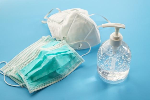 Frasco de gel de desinfetante para álcool com máscara facial n95 sobre fundo azul covid-19 conceito de prevenção de coronavírus