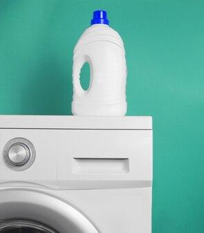 Frasco de gel de lavagem na máquina de lavar contra um fundo azul