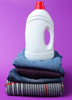 Frasco de gel de lavagem na pilha de roupas na mesa roxa.