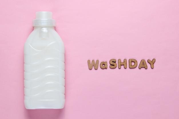 Frasco de gel de lavagem na superfície rosa com o dia de lavagem de texto