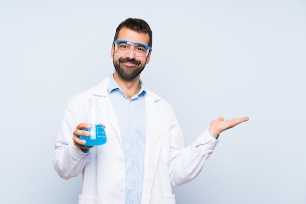 Frasco de laboratório de exploração científica jovem sobre parede isolada, segurando copyspace imaginário na palma da mão para inserir um anúncio