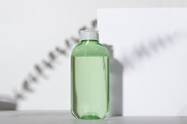 Frasco de limpador facial. loção ou água micelial para limpar o rosto em um fundo branco com sombras fortes de um galho de planta. produto cosmético líquido em embalagem verde.