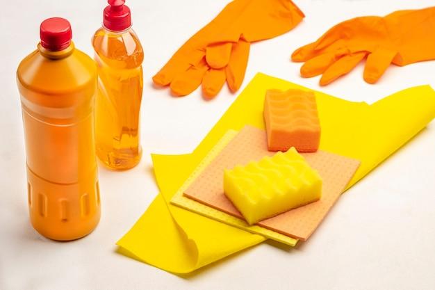 Frasco de líquido laranja, esponja amarela e pano amarelo. luvas de borracha laranja. produtos químicos domésticos para limpar o apartamento. fundo branco. vista do topo
