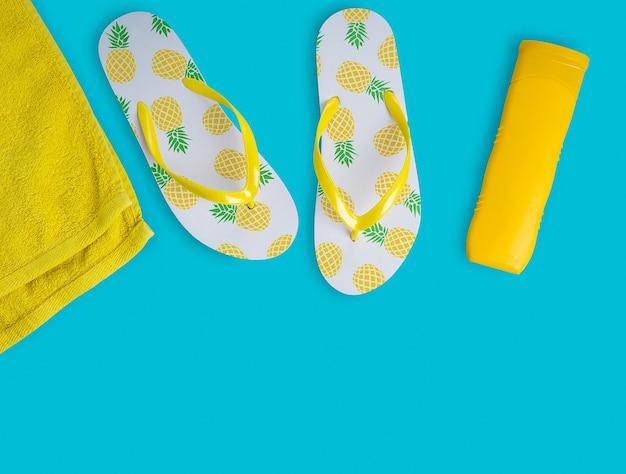 Frasco de loção de protetor solar amarelo brilhante chinelos brancos e toalha de praia em fundo azul-celeste vívido