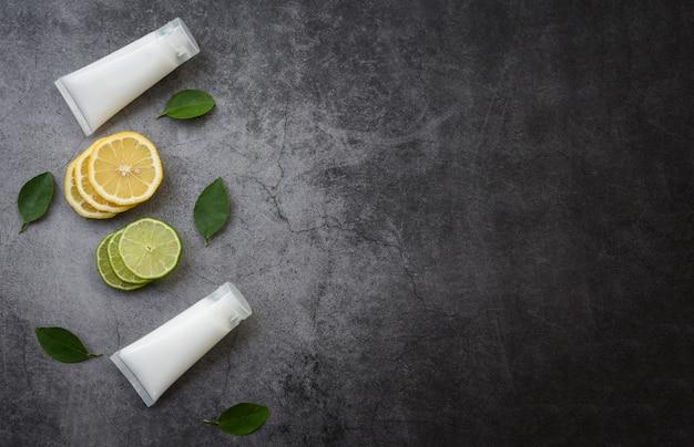 Frasco de loção natural para remédios de beleza de rosto e corpo e estilo de vida orgânico minimalista com fatia de limão e formulações de ervas de folhas verdes em fundo preto