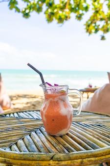 Frasco de manga, abacaxi, melancia e iogurte ou smoothies de iogurte com praia de mar Foto Premium