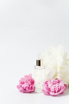 Frasco de maquete de vidro transparente com conta-gotas com soro cosmético, óleo, essência entre flores de peônia rosa e branca em branco
