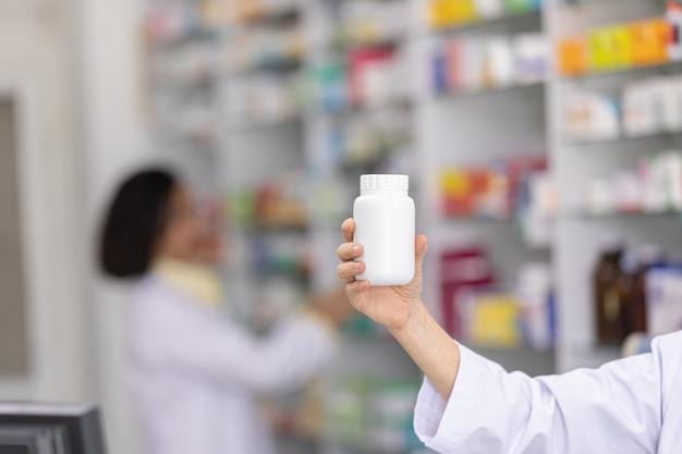 Frasco de medicamento branco na mão farmacêutico