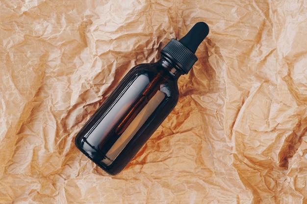 Frasco de óleo cbd, tintura de ácido hialurônico em papelão amassado